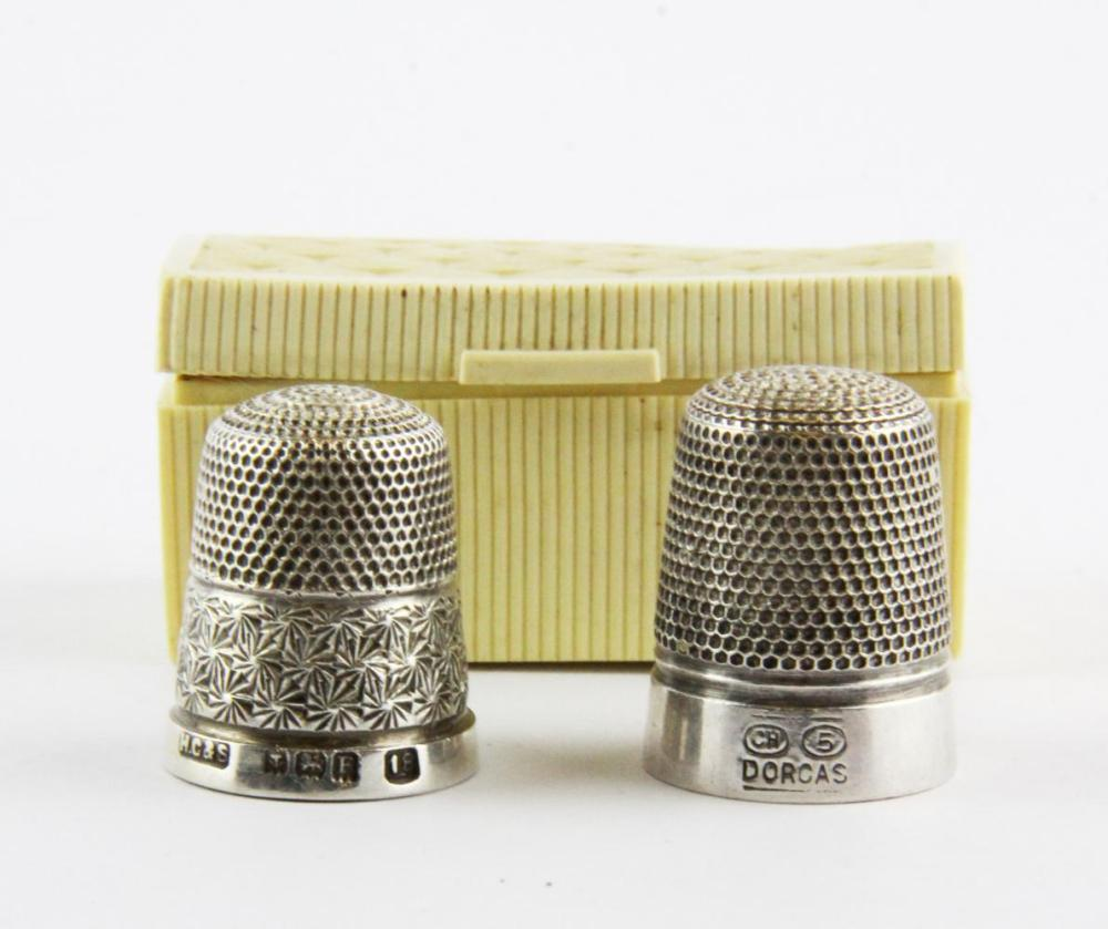 A 1920's celluloid box containing a hallmarked silver thimble and a further white metal thimble stamped CH.