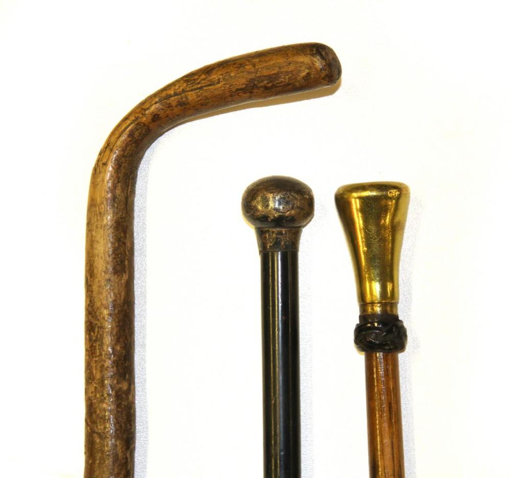 A hallmarked silver topped walking cane, a weighted club top walking cane and walking stick.