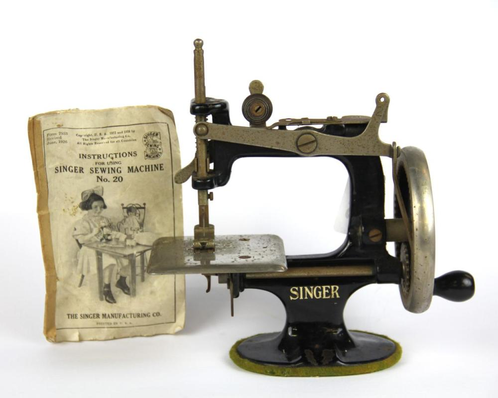 A 1926 Century miniature American Singer sewing machine with original instructions, H. 18cm.