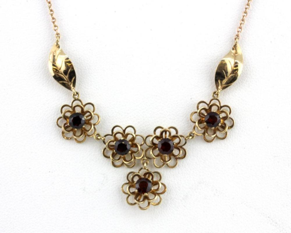 A 9ct yellow gold garnet set flower shaped necklace, L. 40cm.