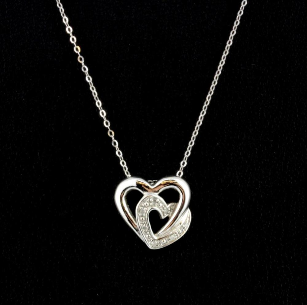 A boxed 9ct white gold diamond set heart shaped  pendant and chain, L. 1.2cm.