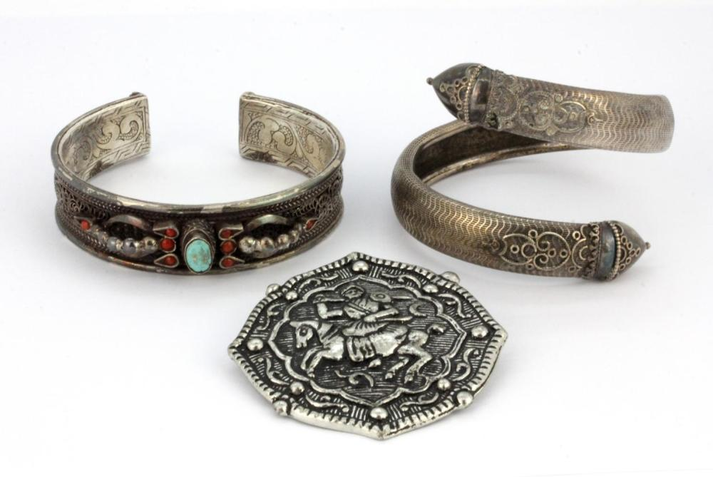 Two Oriental white metal bangles and a white metal brooch.