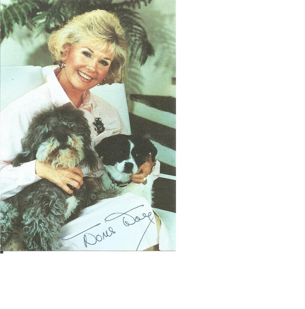 Doris Day signed 6 x 4 colour photo, seated with her two dogs. Comes with biography information.
