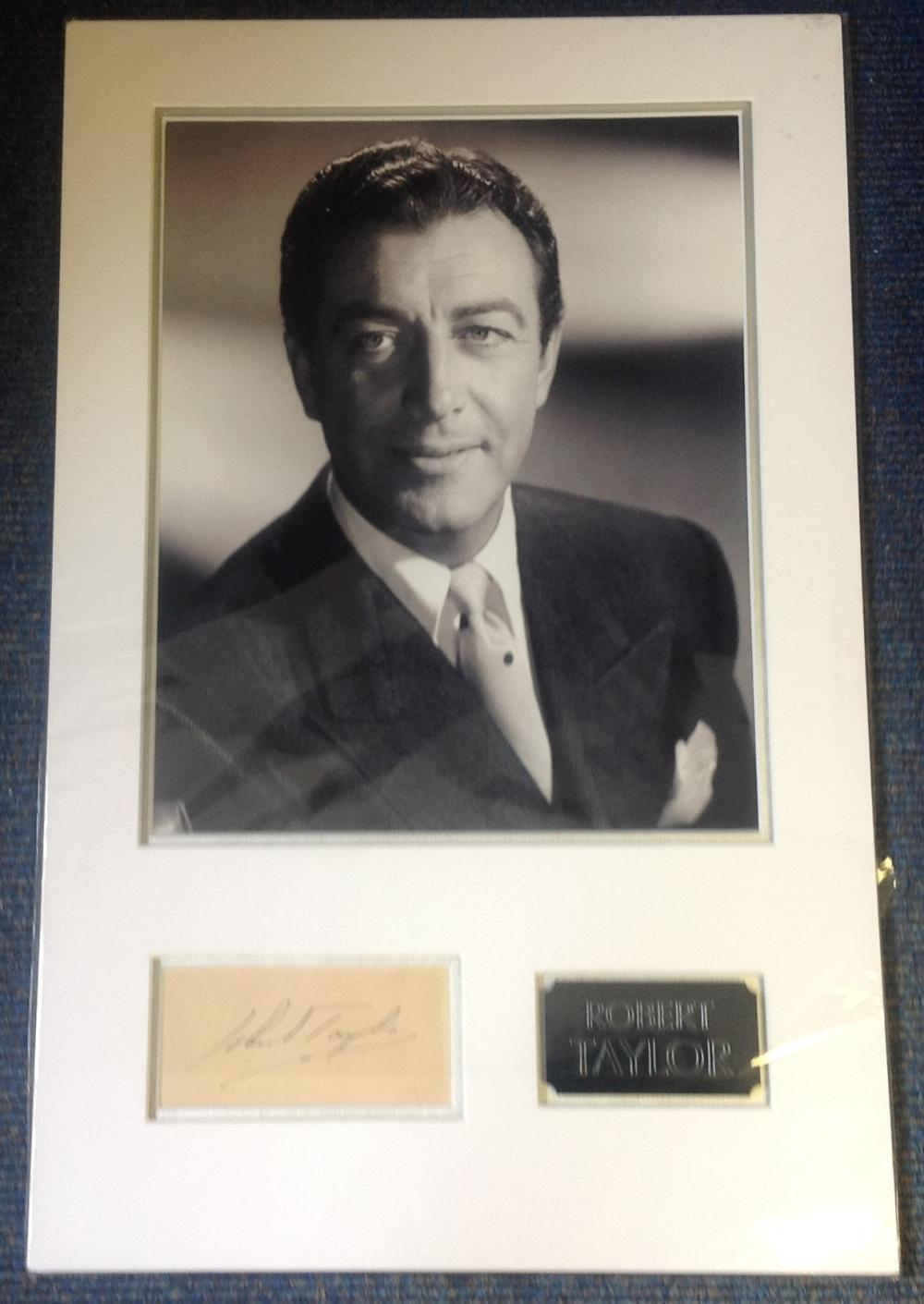 Robert Taylor signature piece mounted below b/w photo. Approx overall size 23x14. Good Condition.