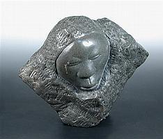 John Takawira (Zimbabwean, 1938-1989), a polished stone carving of a sleeping face within a polished boulder,