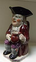 A late 18th/early 19th century pearlware toby jug,