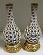 A matched pair of Royal Worcester reticulated bottle vases, date letters for 1879 and 1884,