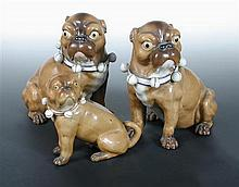 A pair of and a smaller late 19th century German porcelain pug dog,