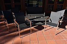 A four piece stainless steel frame outdoor lounge suite with coffee table.