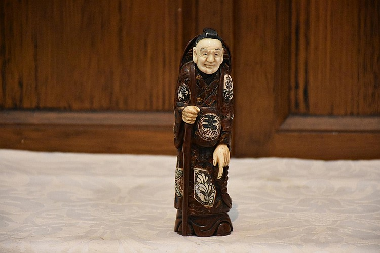 A superb Japanese 19th century ivory and hardwood figure of the noble gent with staff, signed with coral seal to base. Height 17cm, Width 5cm