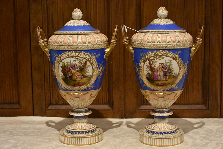 A good pair of 19th century Royal berlin lidded vases having hand painted central panels of the courting couple with gilt highlights. Height 34, width 21 cms.