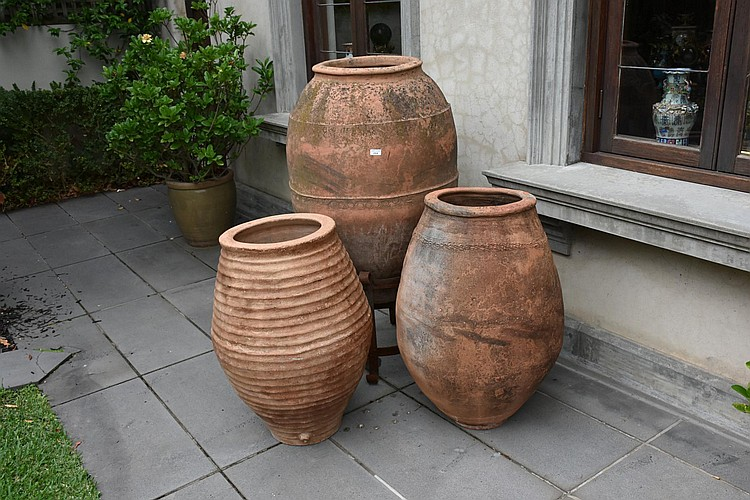 Three Large terracotta outdoor urns, One supported on wrought iron base. Height 134, width 75cms.