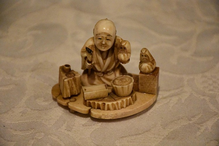 A Chinese 19th century ivory figure depicting the artisan at work.