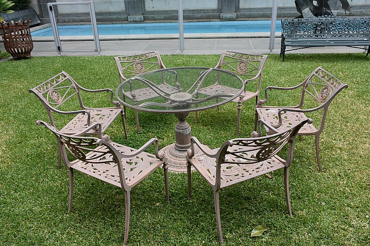 A lovely cast iron based outdoor circular garden table fitted with a glass top and having six matching outdoor cast iron chairs. Height 70cm, Width 108cm
