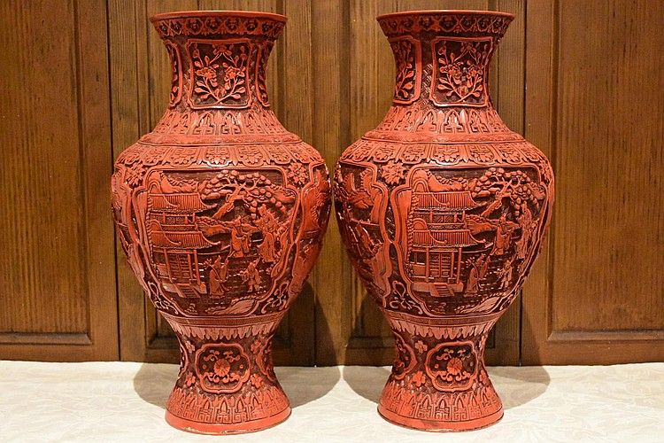 A good pair of Chinese cinnabar lacquer vases having carved figures in landscape decoration. Height 47, width 26cms.