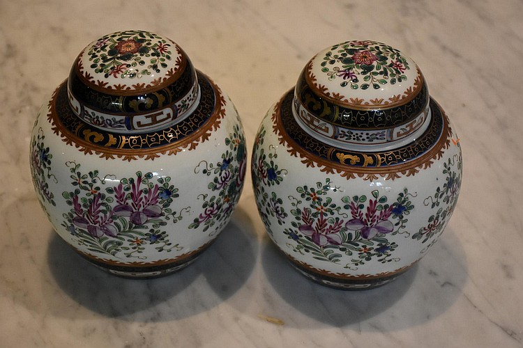 A good pair of Chinese lidded vases having all over floral decoration. Height 18cm, Width 15cm