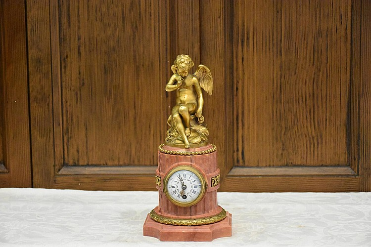 A French 19th century ormolu and rouge marble time piece having ormolu winged cherub mount. Height 25cm, Width 12cm