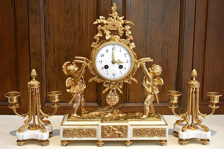 A finest French 19th century ormolu and marble three piece clock set comprising central time piece with cherub supports and side candelabra. Height 39cm, Width 30cm