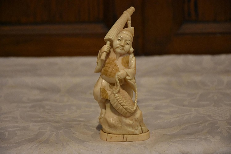 A good Japanese Meiji period hand carved figure of the fisherman with his catch, signed to the base. Height 25cm, Width 6cm
