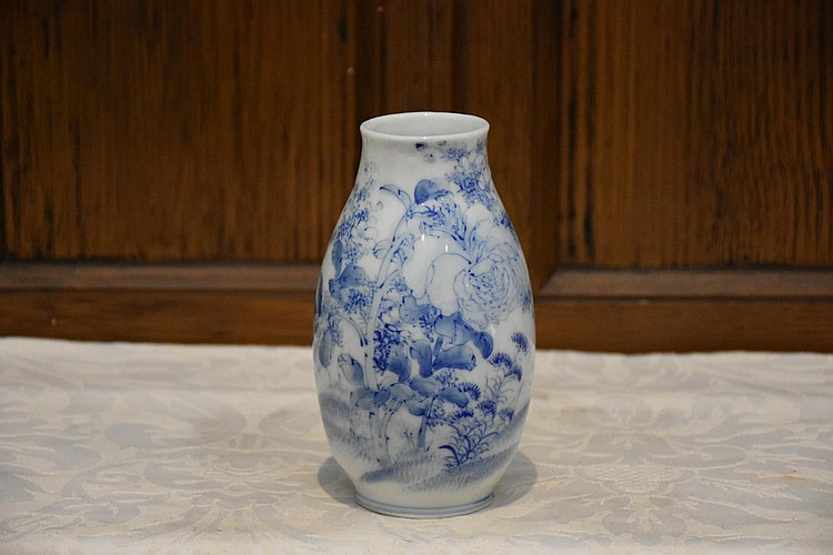A Chinese hand painted blue and white porcelain vase with all over floral decoration. Height 16cm, Width 9cm