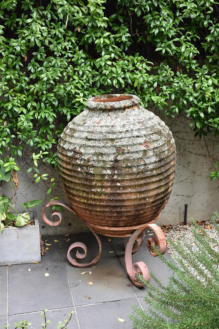 A large outdoor terracotta garden urn supported on wrought iron base. Height 123cm, Width 82cm