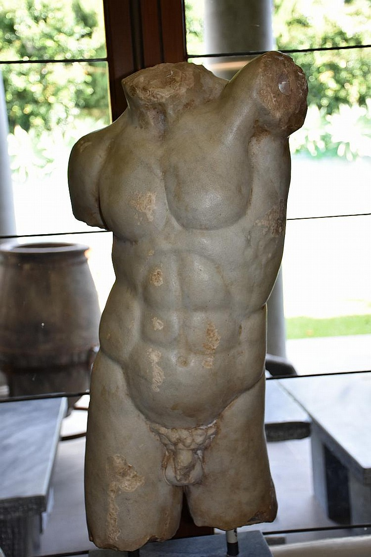 A Roman Marble Male Torso – Circa 3rd Century A.D. after the Roman bronze now in the Museo Nazionale, Naples, and probably base on a Hellenistic original. The life-size marble is close to the antique bronze in every respect, but for an additional