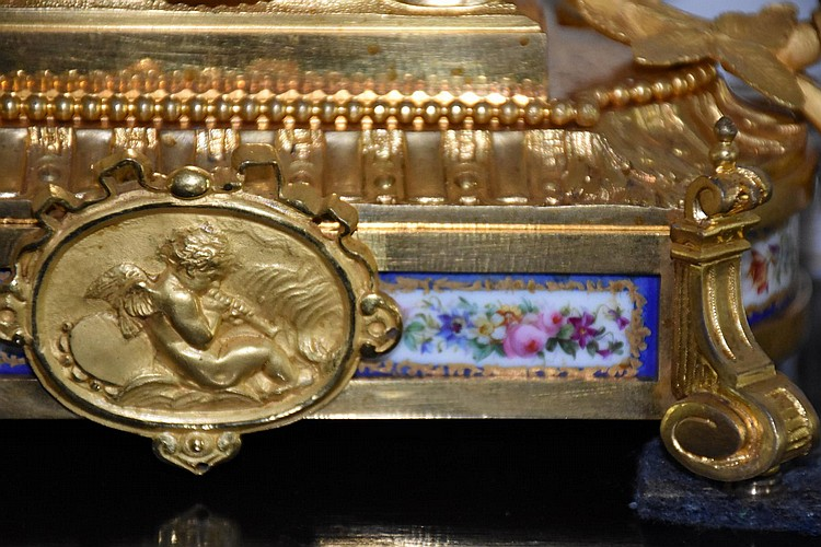 A French 19th century Ormolou salon clock having hand painted Sevres panel and dial depicting cherub and finest ormolu floral mounts. Height 23cm, Width 25cm
