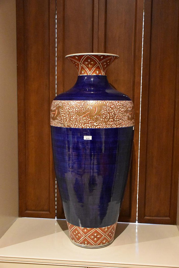 A wonderful and large pair of 19th century blue Japanese porcelain vases having hand painted phoenix decoration and gilt highlights. Height 109, width 47 cms.