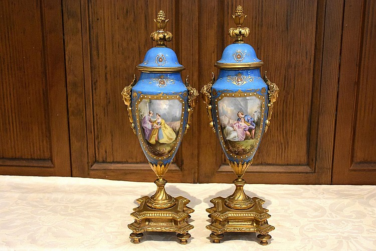 A superb pair of French 19th century Sevres and ormolu urns having jewelled decoration and central panels depicting the courting couples. Height 37cm, Width 13cm