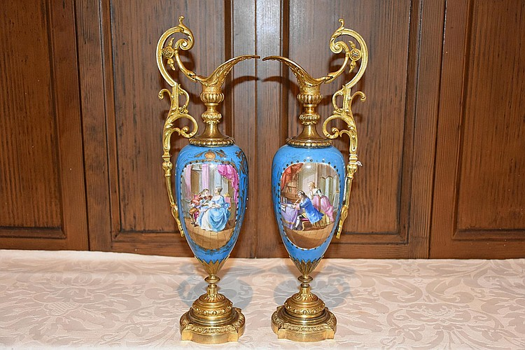 A fine pair of French 19th century Sevres and ormolu ewers having hand painted decoration of the romantic couples. Height 39cm, Width 13cm