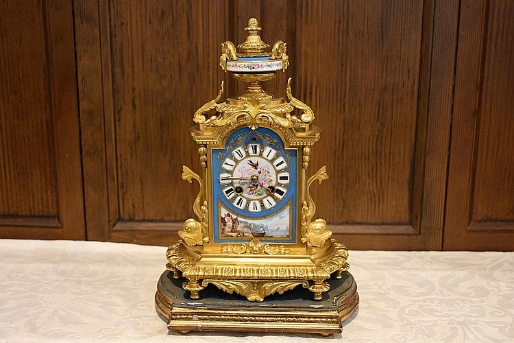 A fine French 19th century Sevres salon clock having all over ormolu mounts, hand painted decoration of the romantic couples and supported on a giltwood base. Height 36cm, Width 25cm