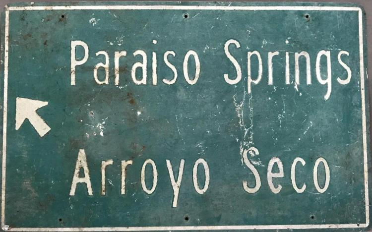 Directional road sign for Paraiso Springs Road and Arroyo Seco road sign