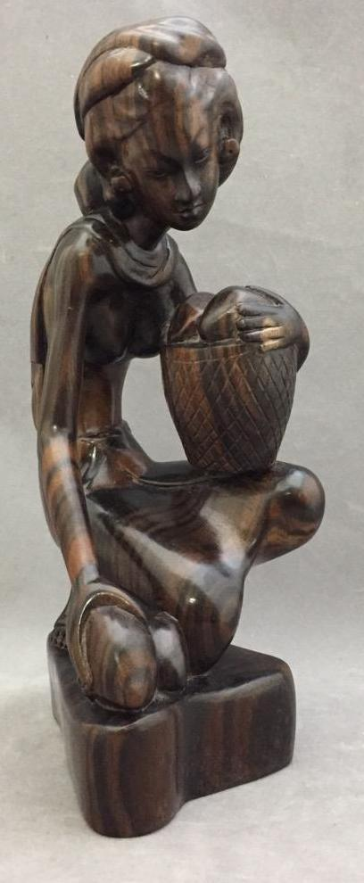 Fine hand-carved exotic wood statue of woman gathering with basket
