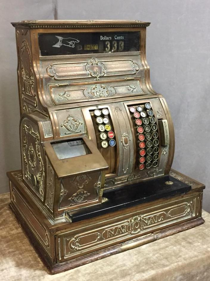 Ornate antique National cash register w/brass body & oak base