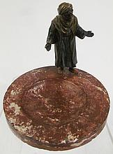 COLD PAINTED SPELTER FIGURE OF AN ARAB MERCHANT ON THE EDGE OF A RED MARBLE DISH