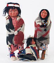 THREE SKOOKUM DOLLS. Various children with a