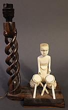 AFRICAN (CONGO) CARVED IVORY FIGURE OF A NATIVE DRUMMER.  Mounted with  an open spiral carved hardwood lamp.  The figure is 6 1/4