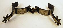 PAIR OF COWBOY SPURS.  Wrought iron with engraved outside panels and brass rowel ls.