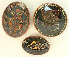 NED FOLTZ REDWARE SLIP DECORATED POTTERY.  Three black ground floral designs.  L