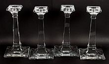 Four colorless glass candlesticks