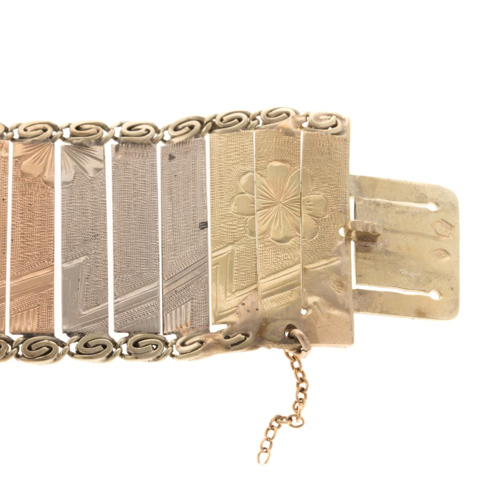 Lot 137: A 14K Tri Colored Engraved Wide Link Bracelet