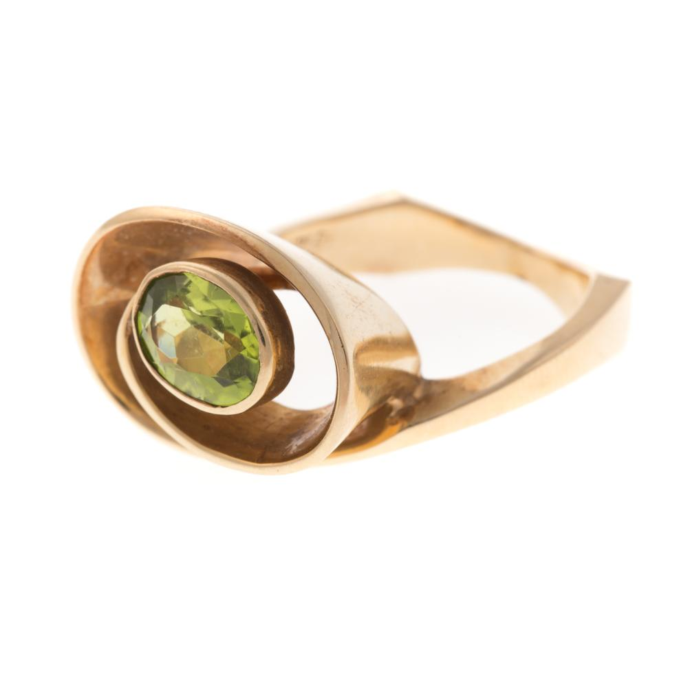 A Ladies 14K Contemporary Swirl Ring with Peridot