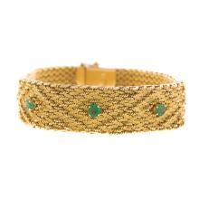 Lot 224: A Ladies Wide 18K Woven Bracelet with Emeralds