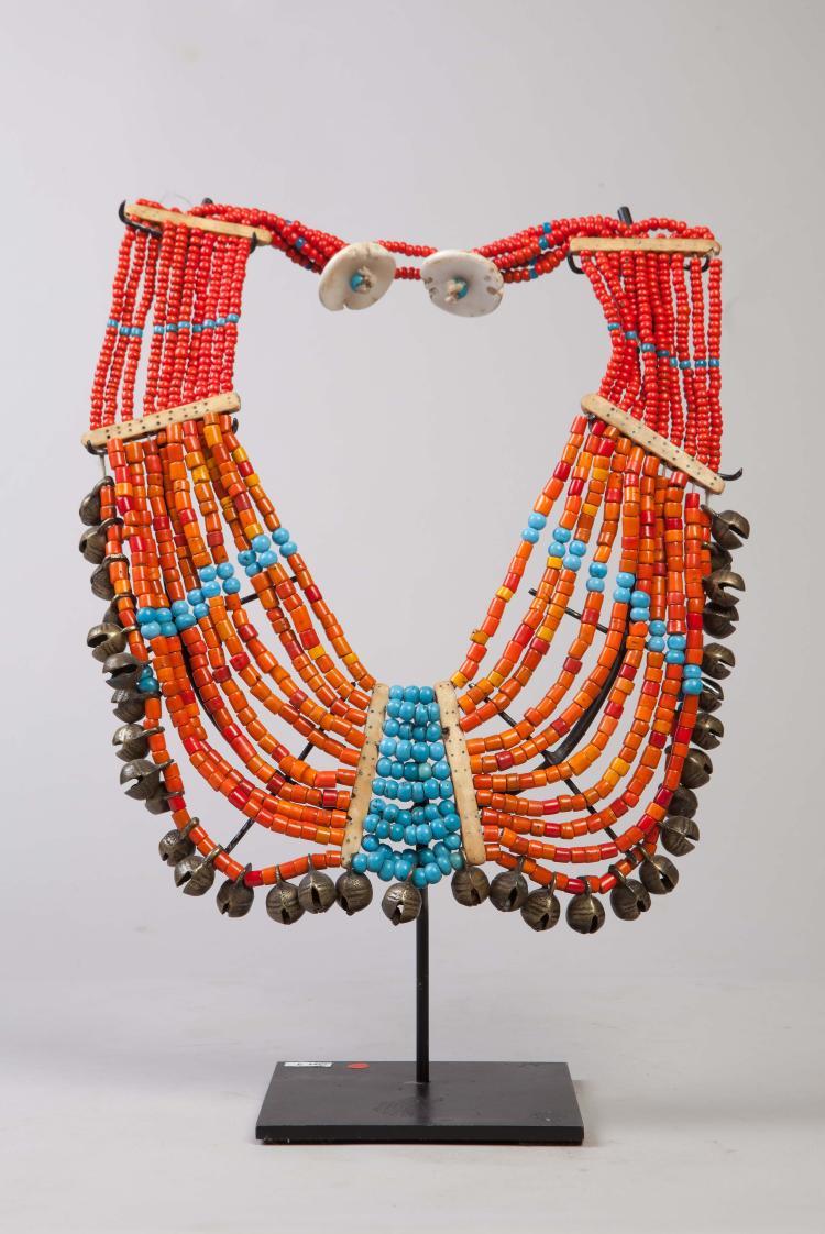 Pectoral Naga composé de dix rangs de perles de pate de verre couleur turquoise et corail séparées par des clefs d'os  terminée par une rangée de grelot de bronze et d'un fermoir en coquillage.
