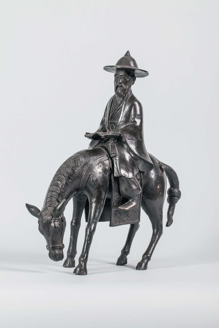 Le sage Toba sur sa mule coiffé d'un chapeau,