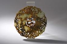 Disque Bi composé de deux cercles concentriques travaillé en ajour de symboles archaïsants à motifs de dragons à l'extérieur et de perles sacrées en granulations à l'intérieur  finement ciselé au centre d'un dragon lové.