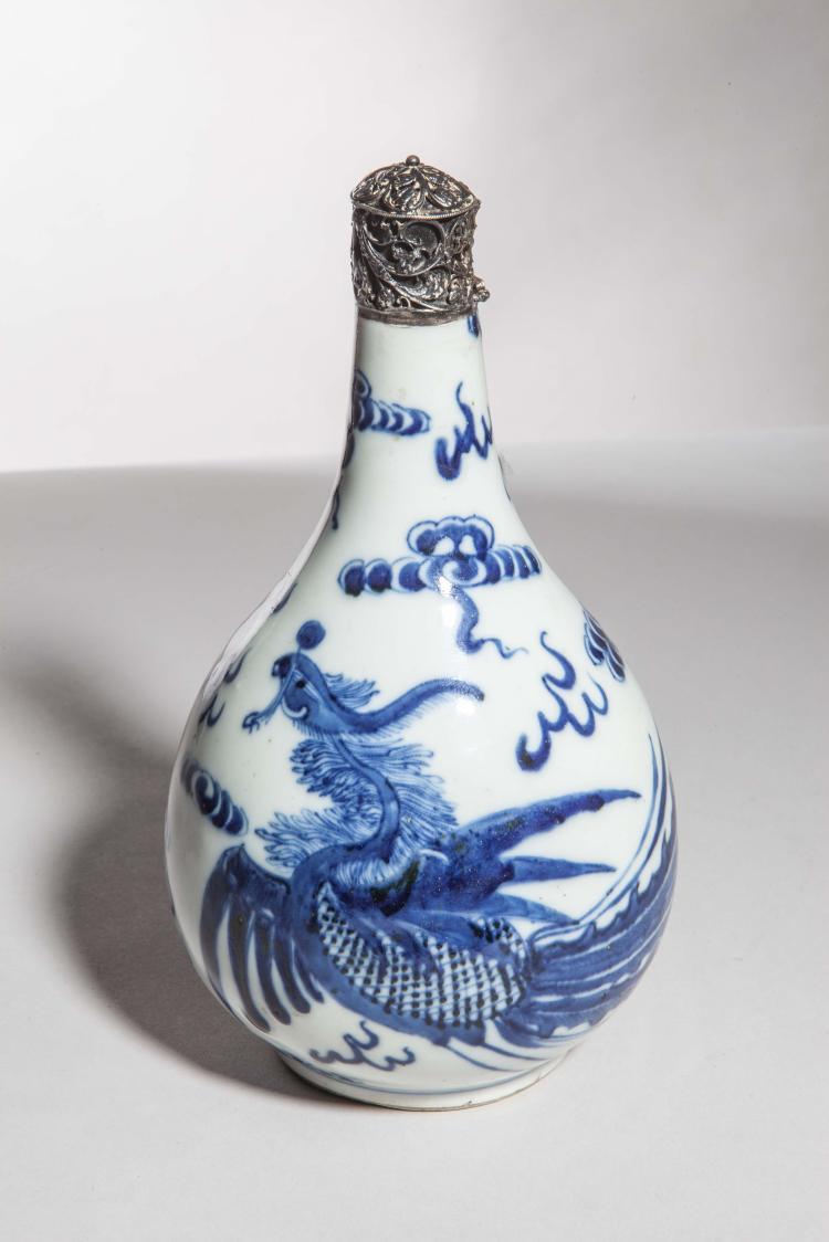 Flacon en porcelaine blanche décorée en bleu cobalt sous couverte d'un Phoenix en vol au milieu de nuages tsi.