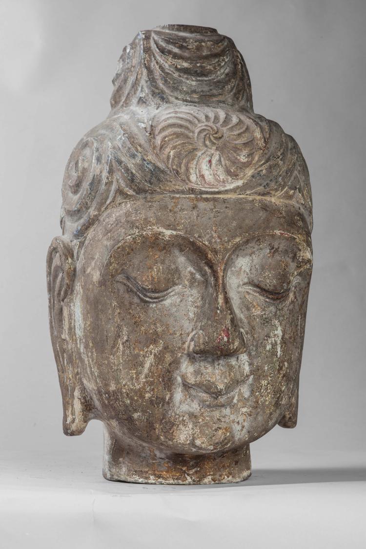 Tête de Buddha à l'expression sereine coiffée d'un chignon ushnisha et d'une chevelure organisée en lignes parallèles ornée d'une rosace centrale.