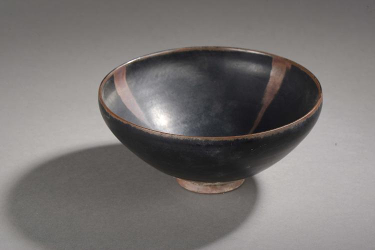Coupe de forme lianzi sur pied en couronne en fin grès porcelaineux à glaçure monochrome noire  ornée de trois coulées brunes.