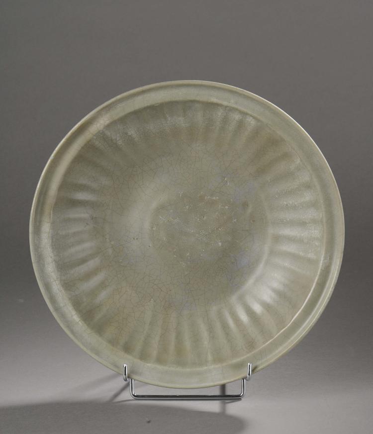 Plat en épaisse porcelaine du longquan moulé de godrons rayonnants au marli sous couverte monochrome céladon craquelé.